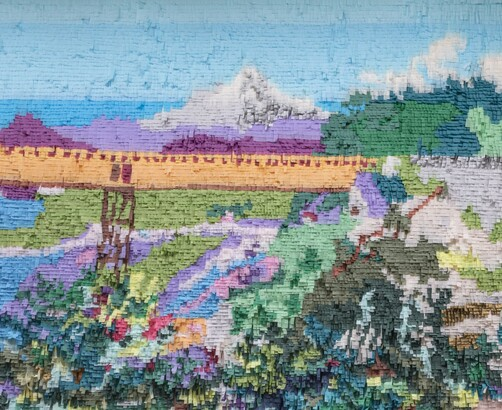 Mountain and bridge made out of colored tissue paper arranged like paint on a wall