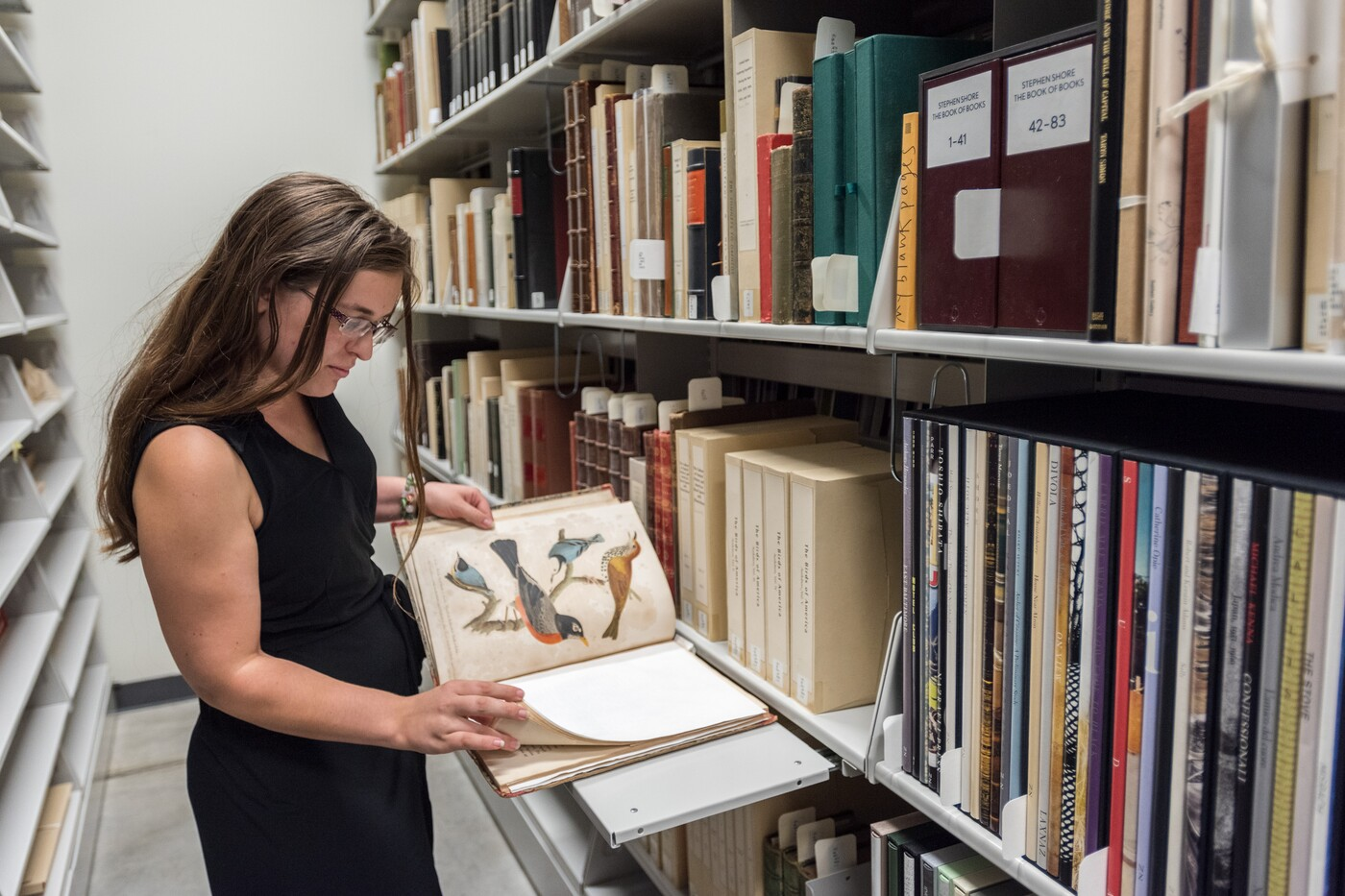 Shelves with archival materials are on the right; on the left a woman has a book open and is reviewing it.