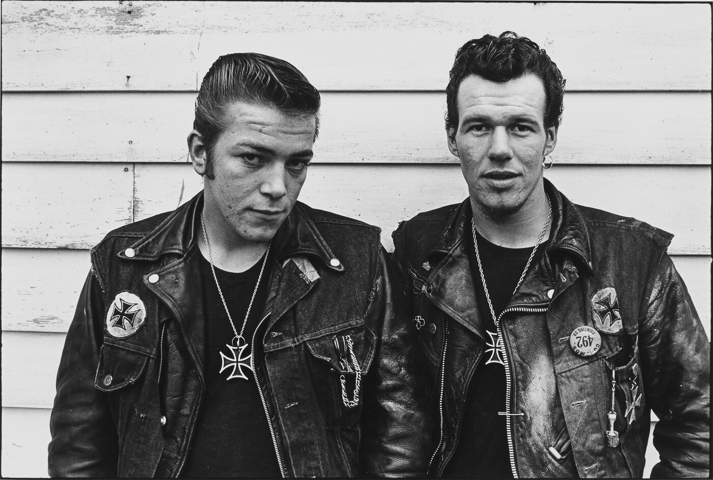 Two motorcyclists with leather jackets against building siding