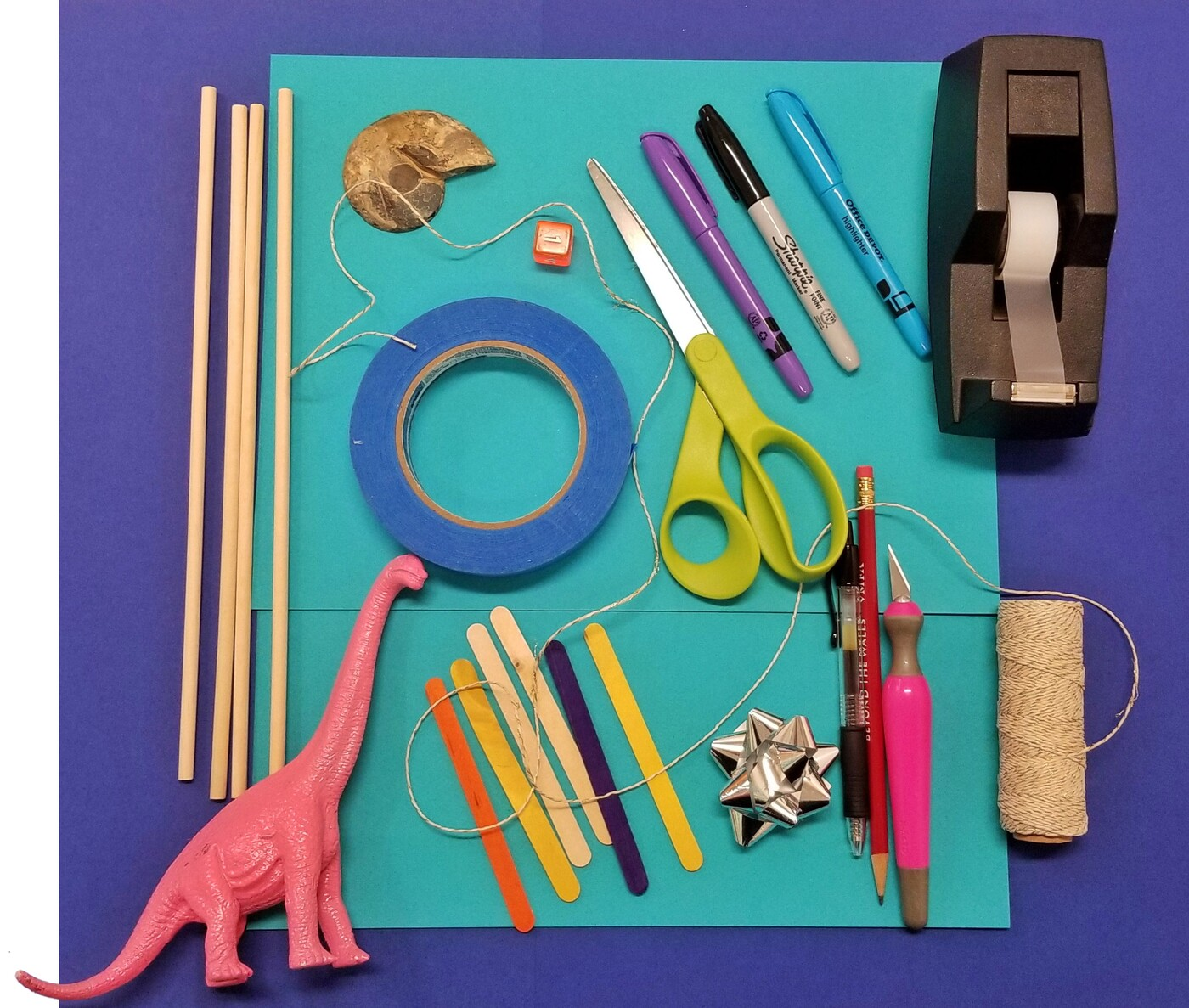 A view of art supplies on a table: wooden dowels, a pink toy brontosaurus, string, a seashell, blue masking tape, popsicle sticks, scissors, markers, pencils, a gold gift bow, a tape dispenser