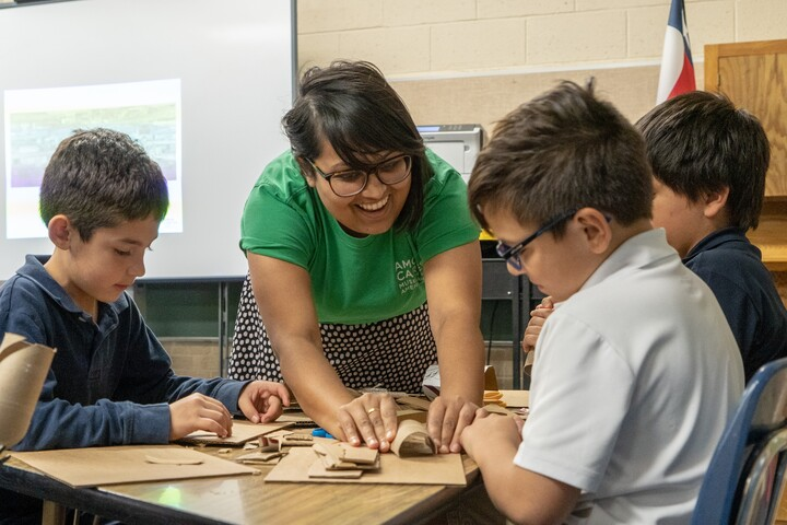 Teacher with three students working on an art project