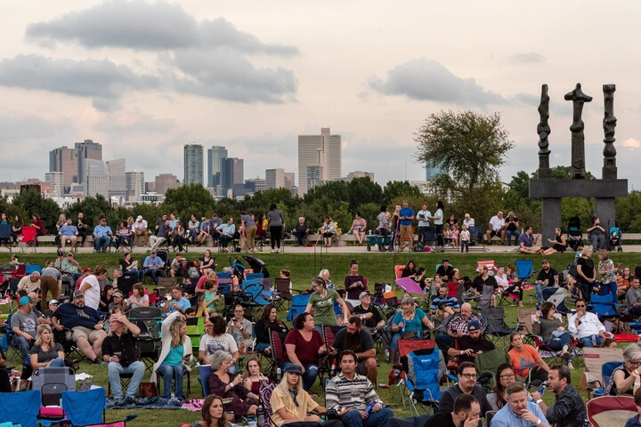 Crowd sits on Carter lawn with Fort Worth skyline and Henry Moore sculpture