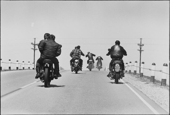 A road with five motorcyclists driving away
