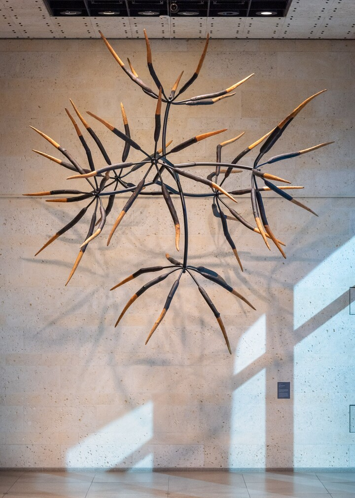 Wooden sculpture of seven parts hangs from ceiling in Carter main gallery