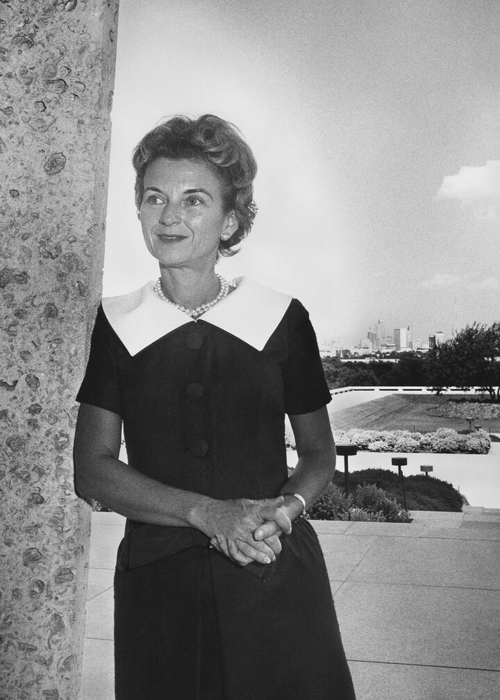 woman in a dress leaning against a limestone column