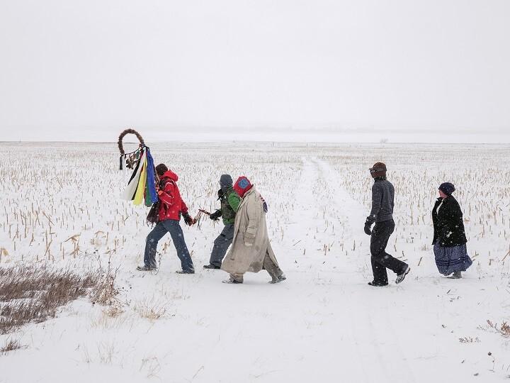 five figures walking through snow