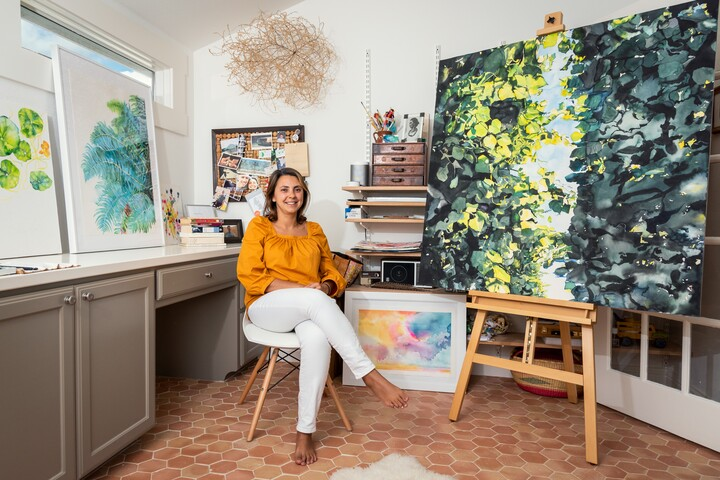 A woman wearing a gold shirt and white pants sits in a studio surrounded by paintings on the wall and on easels