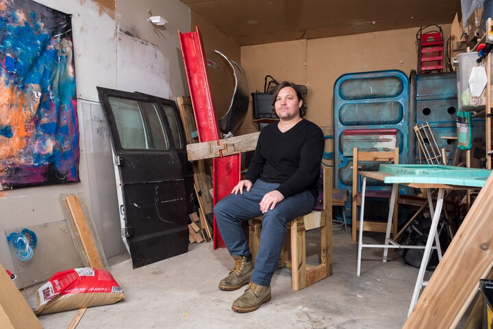 A man in a black shirt and blue jeans sits in a room full of sculptural and found objects