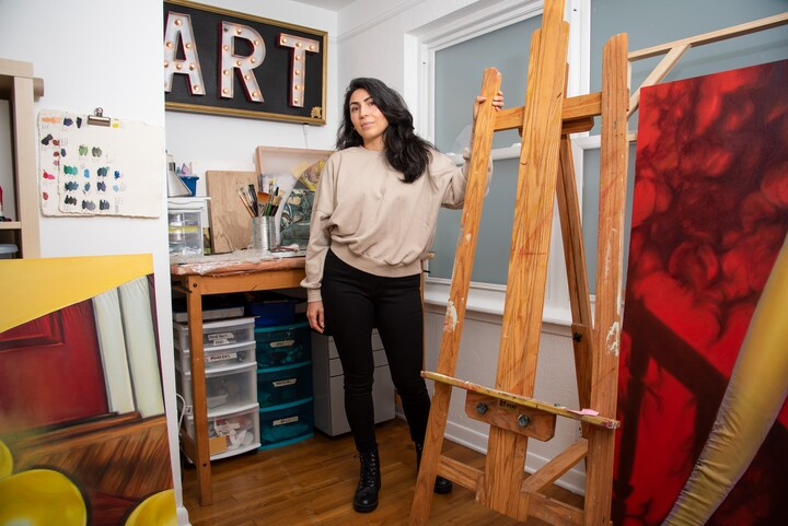 A woman in a tan shirt and black pants stands next to an empty easel in an art studio