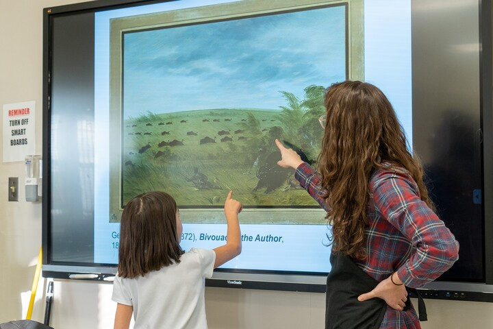 A child stands in front of a screen and points to a detail in an artwork on the screen; an adult standing next to the child points out a different detail