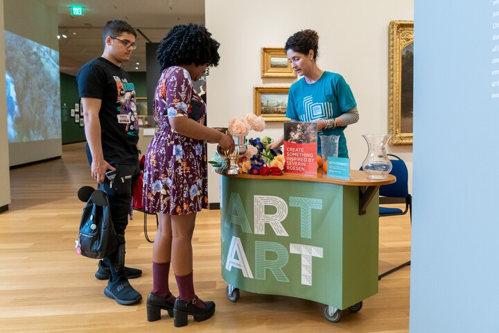 """Two people stand in front of a mobile cart that says """"Art Cart"""" on the front; a staff member behind the cart points out objects on the cart"""