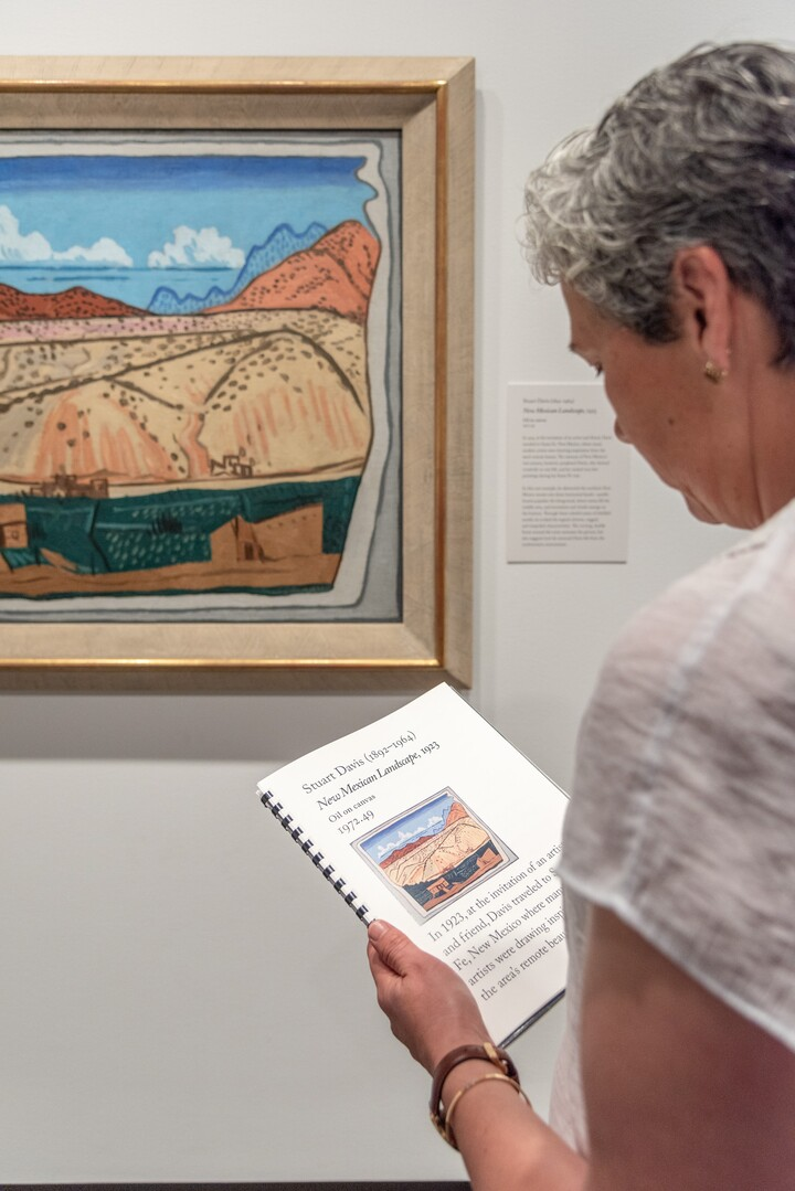 A woman stands in front of a painting; she holds a booklet in her left hand