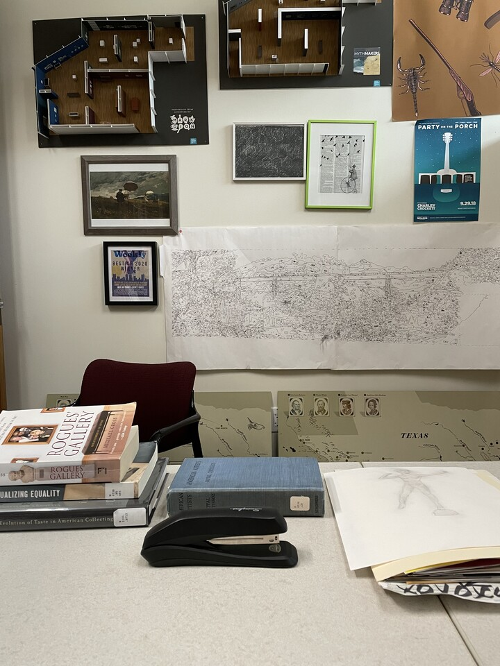 An office desk with (L-R) three library books stacked on top of each other; a cloth covered blue library book; a manilla file folder with papers sticking out of the end; in the foreground is a black Swingline stapler; on the wall behind the desk are maps, framed pictures, and gallery models
