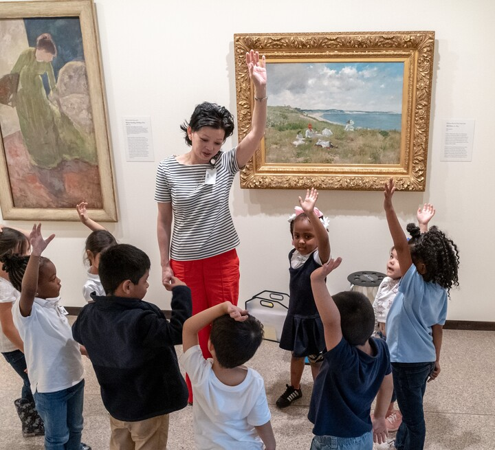 A group of nine children stand facing an adult, who is standing in front of two hung paintings. All are raising hands.