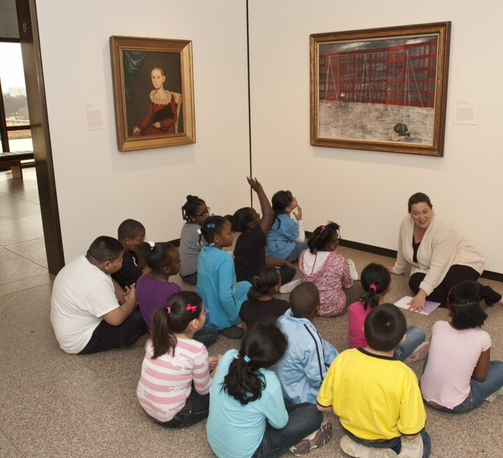 Educator and class sit on the ground in front of Ben Shahn painting