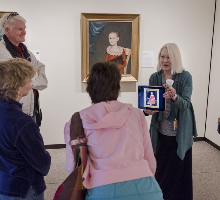 Docent shows iPad and painting to group