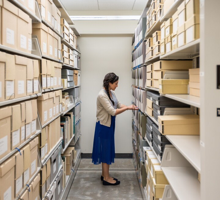 Rows of archival shelves are on either side, with a woman in the middle reviewing material.