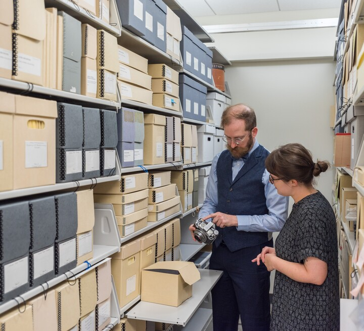 Shelves of archival boxes are on the left. On the right are two people reviewing archival materials.