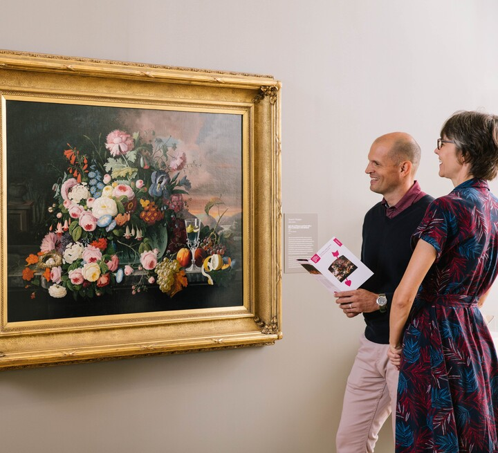 Couple look at a still life painting; the man holds a museum guide in his hands