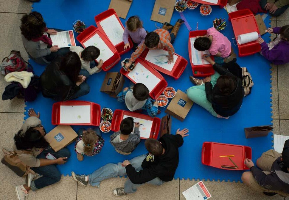 View from above of children and adults sitting on a floor and using red lap desks to create art.