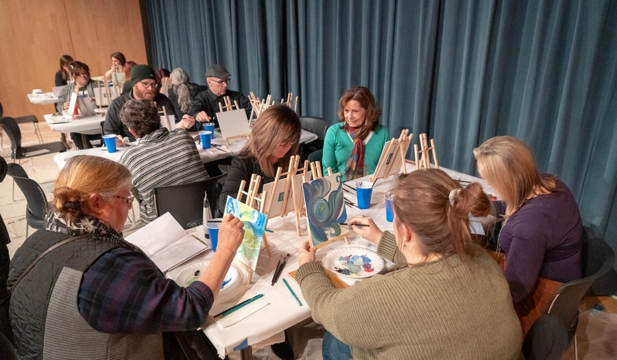 Several teachers are seated around four rectangular tables. Each teacher has a small wooden easel in front of them, on which is mounted a small canvas for painting.