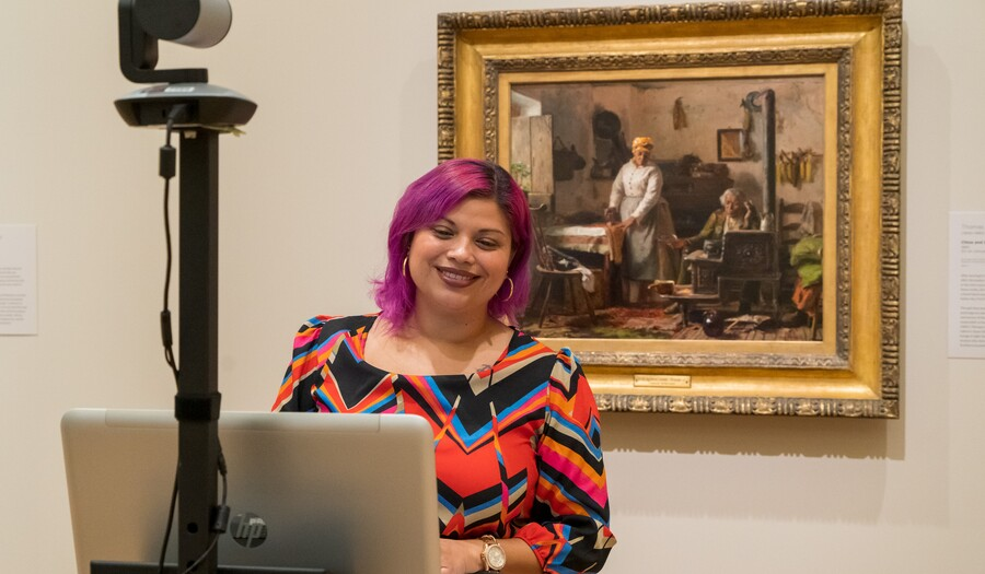 A woman stands between a laptop and camera and a painting