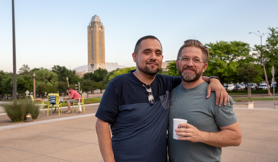 Two men stand on the Carter porch with a drink