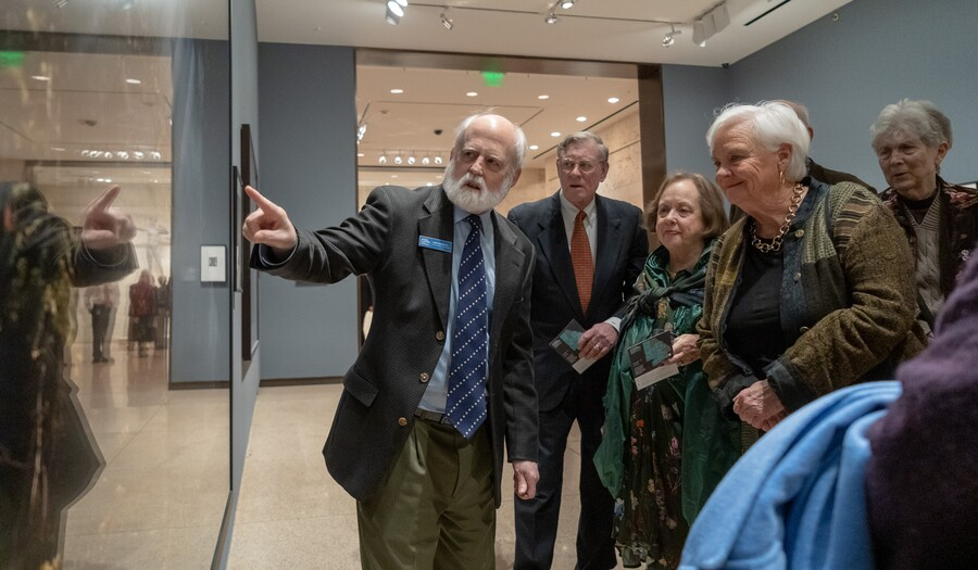 group of people on a tour with a curator in front of a photo