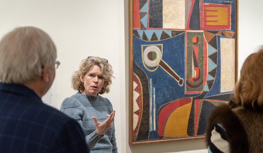 Woman talking to guests in front of Will Barnet's Self-Portrait
