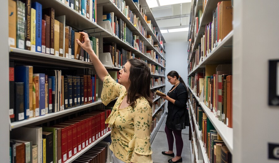 Two women in library stacks