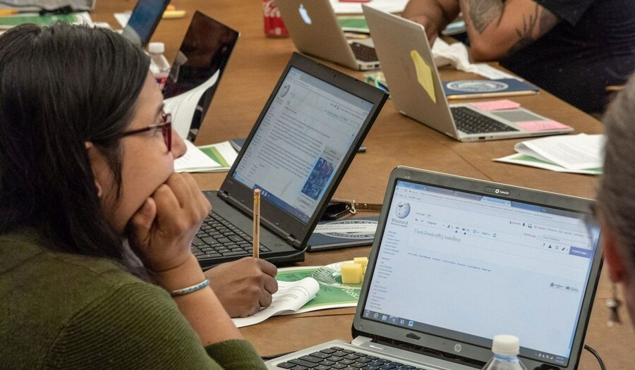 Group sits at table with laptops and research materials