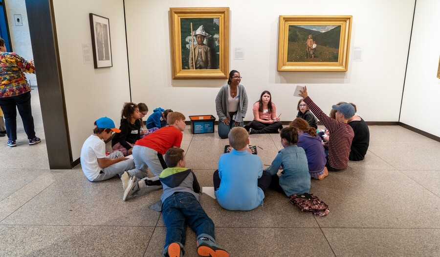Group of children lays and sits on the floor of a gallery with paintings