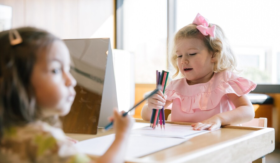 two toddlers coloring with mirrors