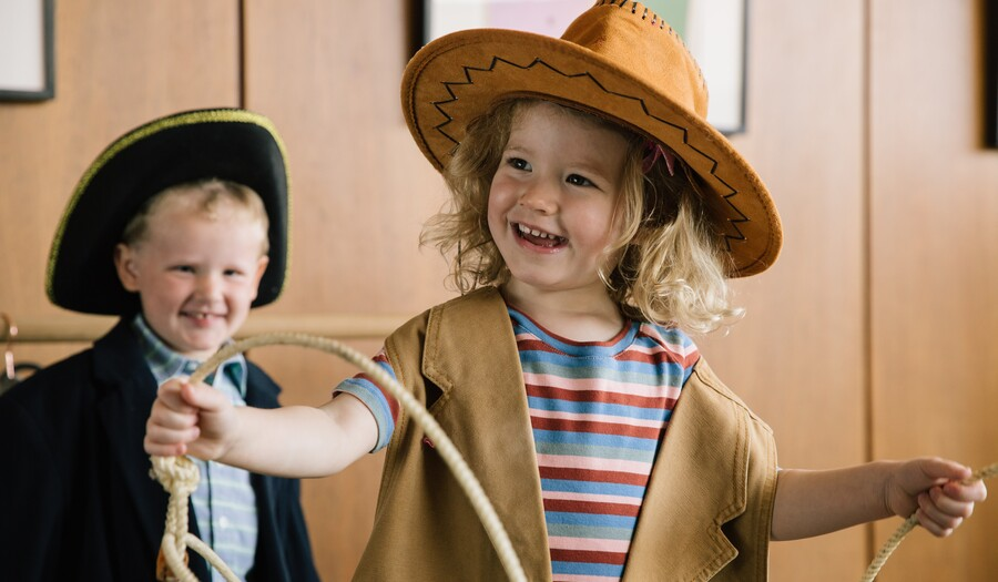 little boy wearing colonial hat and a little girl dressed as a cowgirl