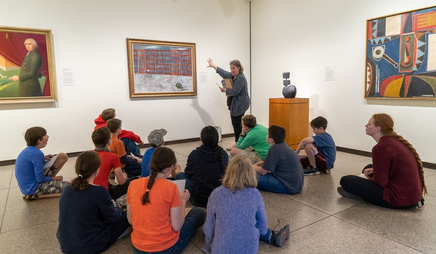 Woman standing in a gallery motions toward painting while group of children and teens sits on the floor