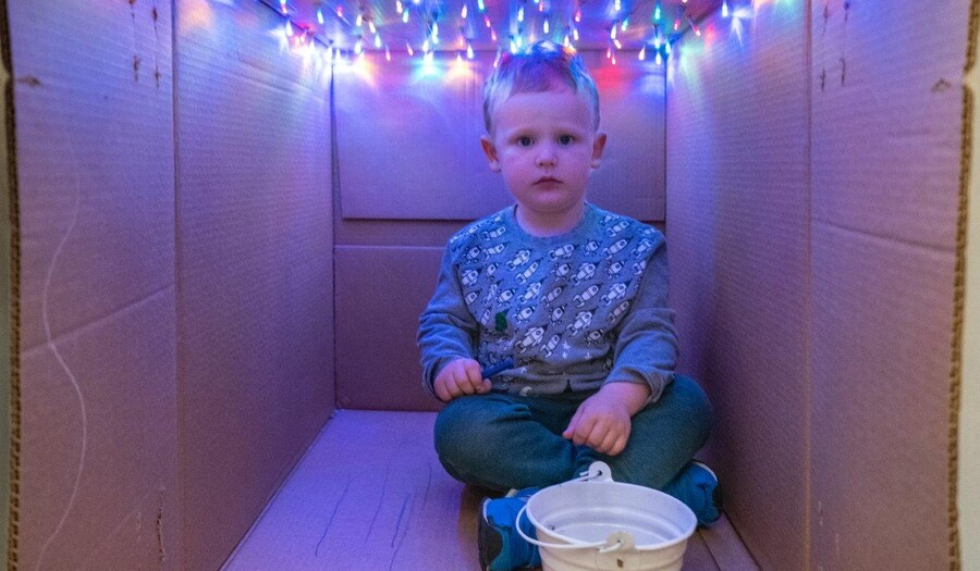A small child sits inside a box; colored lights hang from the ceiling of the box and a white bucket of crayons sits in front of the child