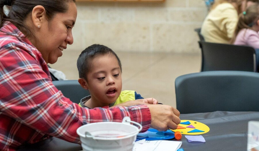 A woman helps a little child with an art project
