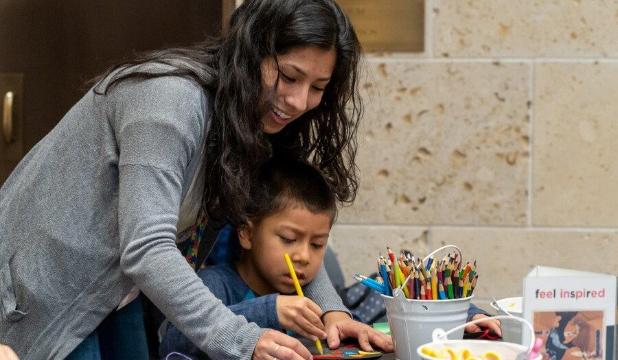 A woman leans over a small child who is sitting at a table working on an art project
