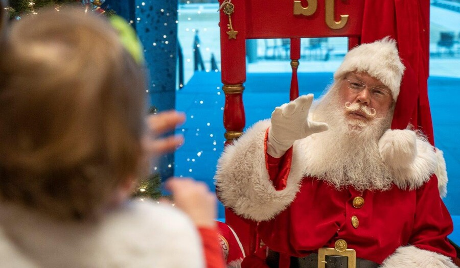 Santa Claus waves to a small child in the foreground who is being held by someone out of view