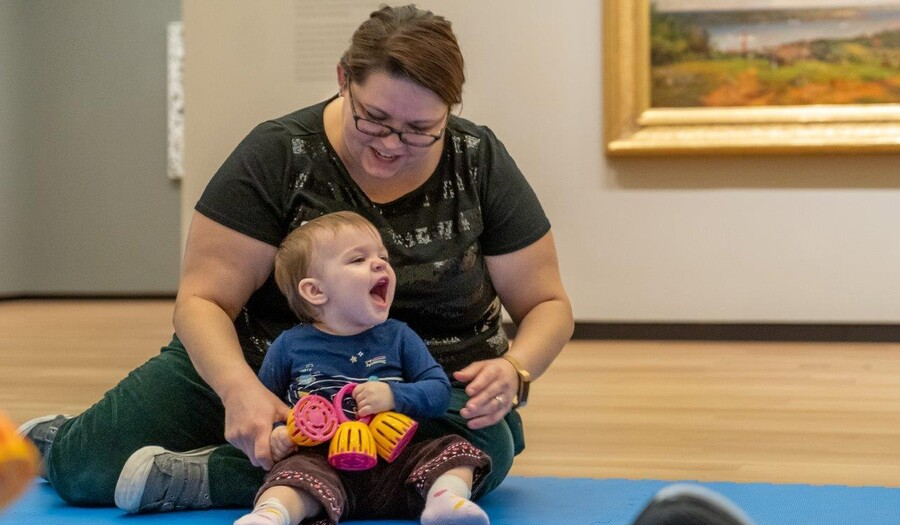 A woman sits on the floor and holds a laughing baby in her lap
