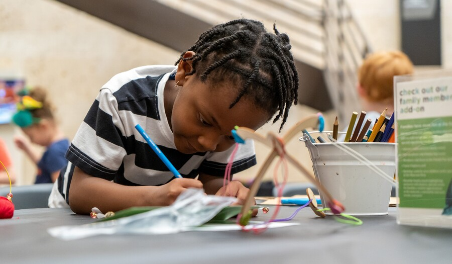 A child sit at a table and intently leans over an art project he is working on