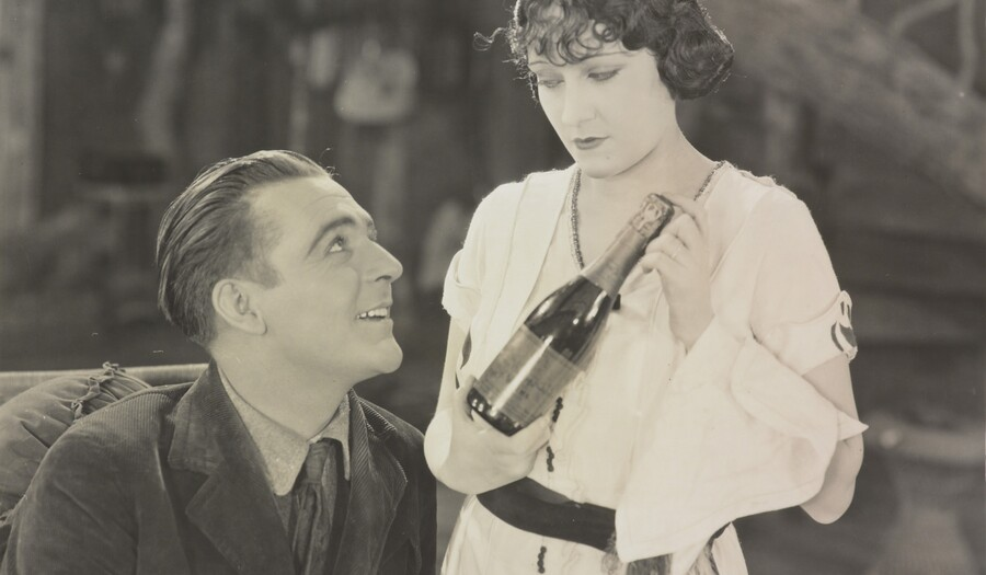 Black and white photo of a seated man looking up at a woman standing next to him holding a bottle of wine