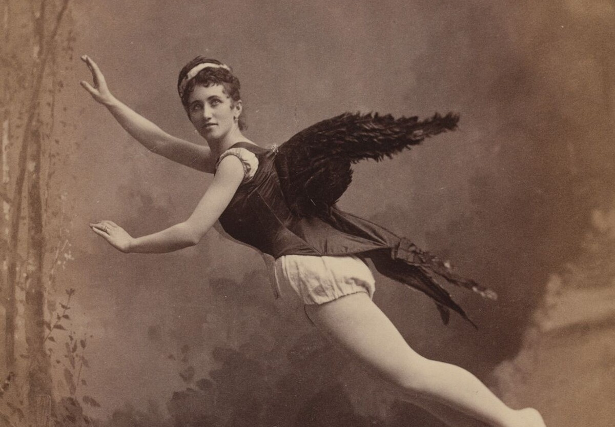 Black-and-white photograph from the 1880s of a woman wearing a dark corset with black feathered wings attached to the back and posed as if she is flying