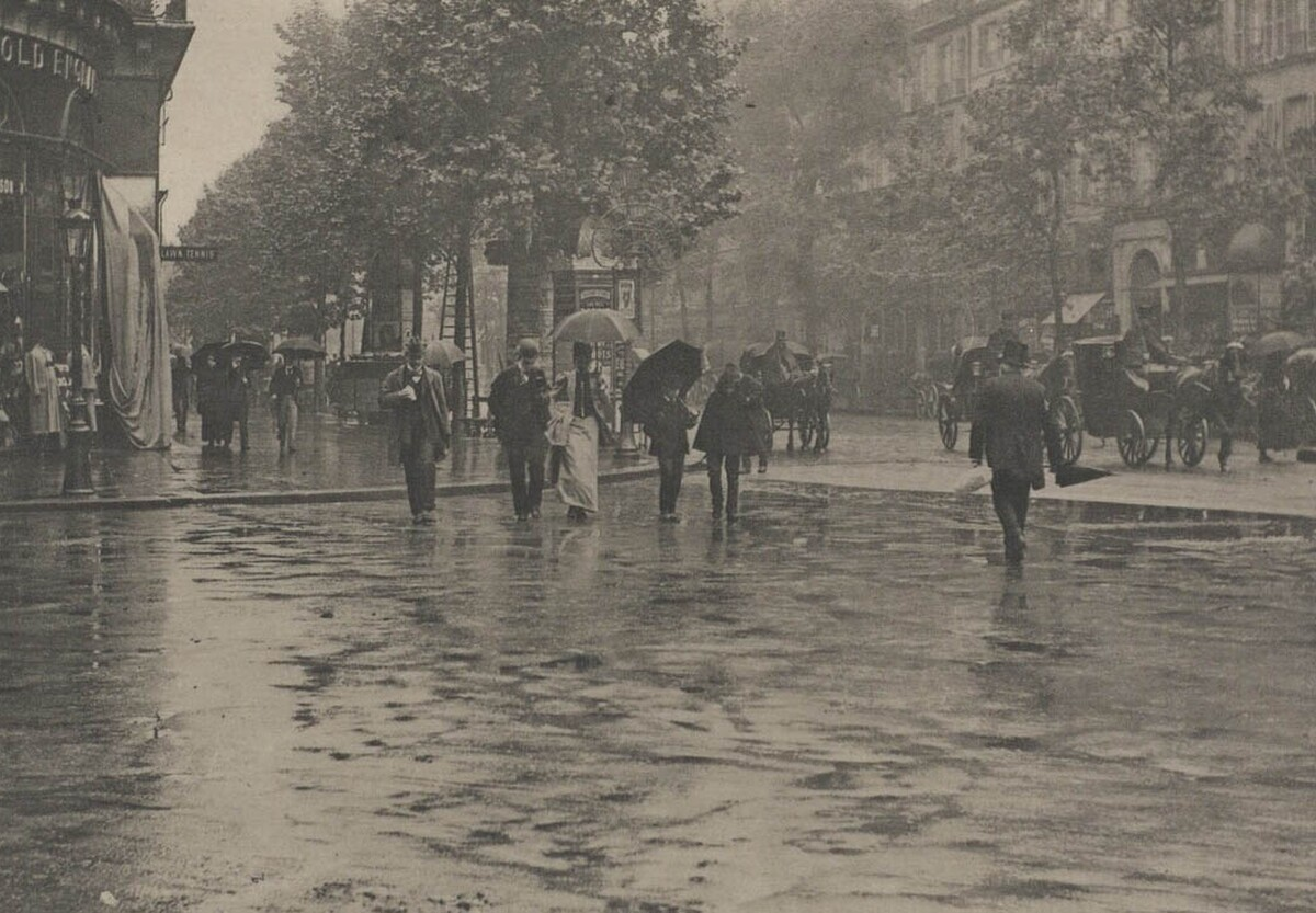 Photo from the 1920s of people walking along a wet street in Paris